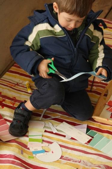 preschooler cutting along lines on paint chip sample