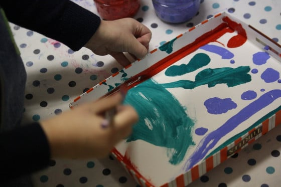 tempera paints, paint brush, box lid, toddler hands