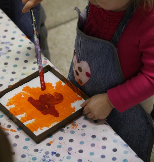 toddler painting orange and red in lid of box