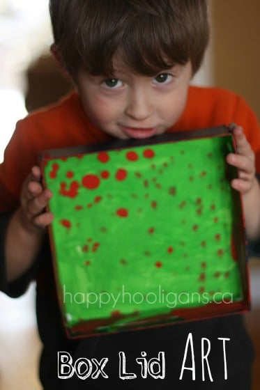 Preschooler holding green and red art painted in box lid