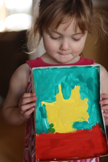 preschooler holding painting of yellow sun in box lid