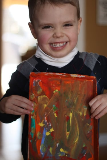 toddler boy holding art painted in box lid