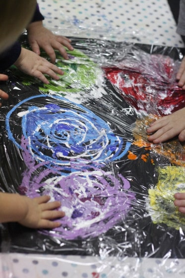 Painting covered in plastic wrap for kids to smoosh