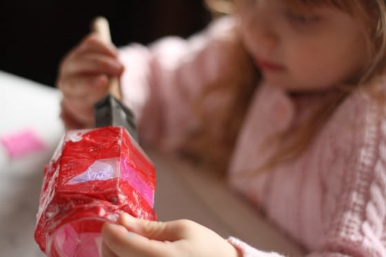 preschooler brushing glue over tissue paper on jar