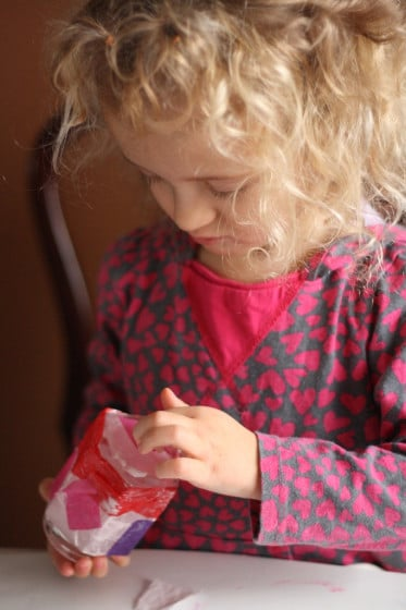 sticking red, pink and purple sucres of tissue paper to jar