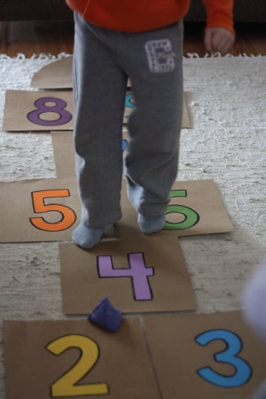 boy jumping on cardboard hopscotch