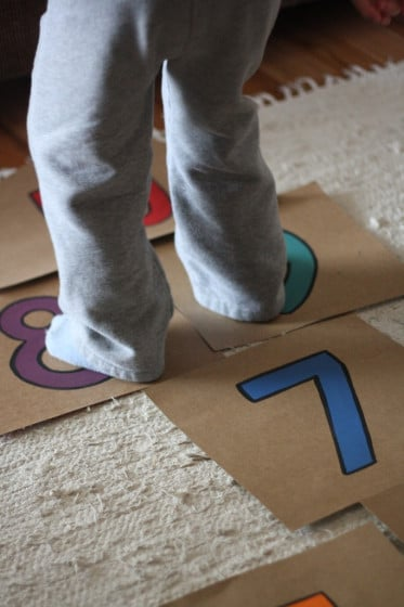 child jumping on cardboard hopscotch on carpet
