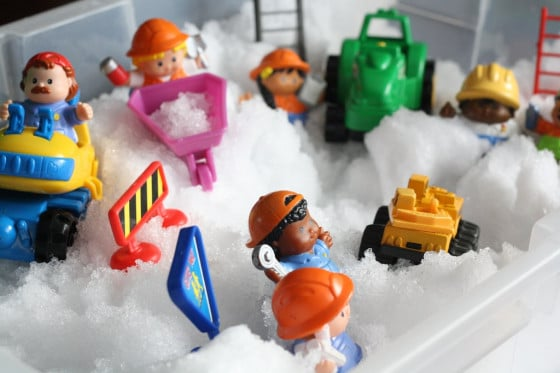 Little People and construction vehicles in a snow sensory bin