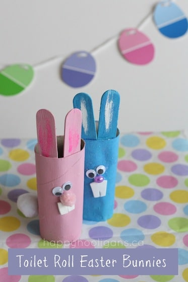 Easter crafts for kids: cardboard roll bunnies in front of a paint chip easter egg garland
