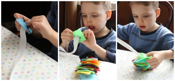 Child developing his fine motor skills by threading felt squares onto button snake.