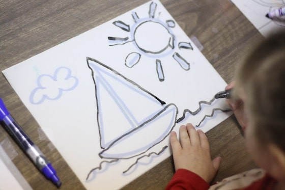 preschooler using tracing paper to draw boat