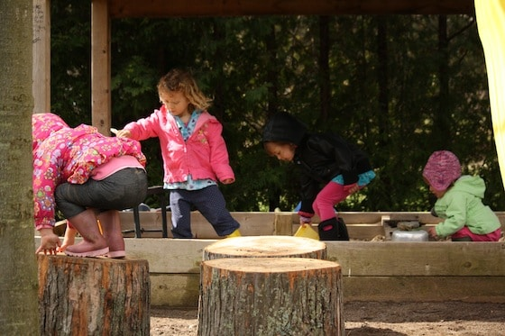 children playing in sandbox and on play logs