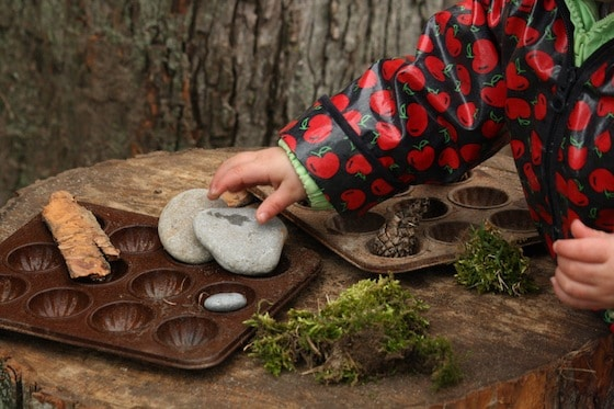 toddler making mud pies on play log