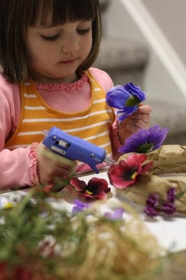 low heat glue gun used by child making paper bag tiara