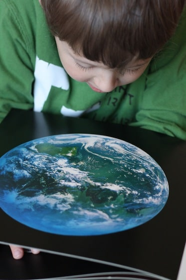 young boy looking at satellite picture of planet Earth