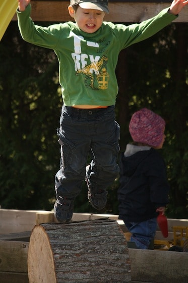 4 year old boy jumping off a play log