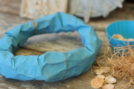 blue paper bag rolled into mermaid crown beside shells and raffia