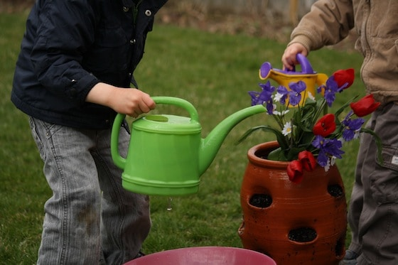 preschoolers pretending to water flowers