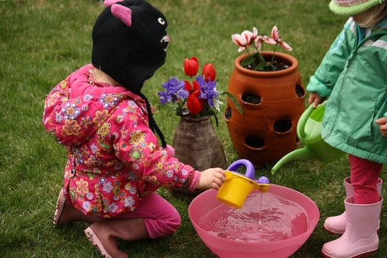 2 toddlers watering fake flowers outside with watering cans
