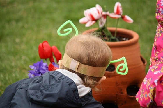 toddler and preschooler looking at artificial flowers in flower pot
