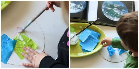 Kids gluing green and blue tissue paper to cardboard circle