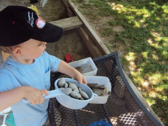 toddler playing with stones in sandbox
