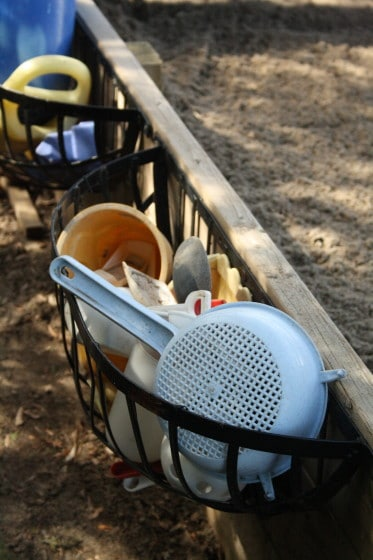 planter baskets hold toys in the sandbox