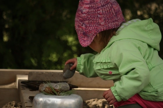 toddler putting stones in bowl in sandbox