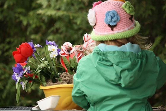 girl playing with artificial flowers in the sandbox