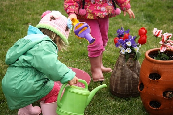 toddlers planting artificial flowers in flower pot
