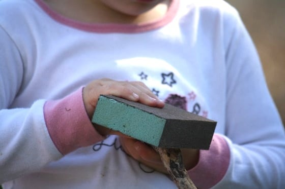 preschooler using sanding blocks and sandpaper