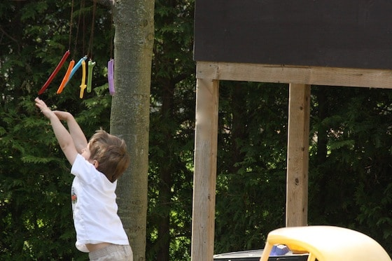child batting at wind chimes beside playhouse