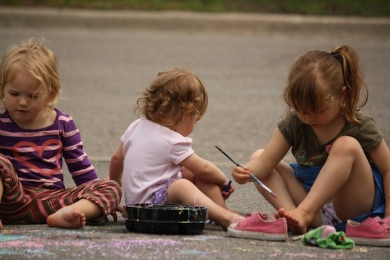 preschoolers painting driveway with homemade chalk paint