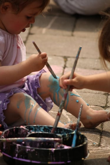Baby painting her legs with sidewalk chalk
