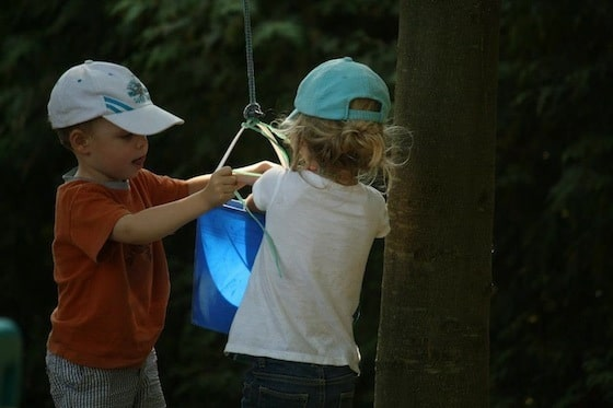 preschool boy and girl playing with bucket and rope pulley system