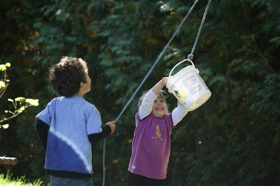 2 preschoolers having fun with the bucket and rope contraption