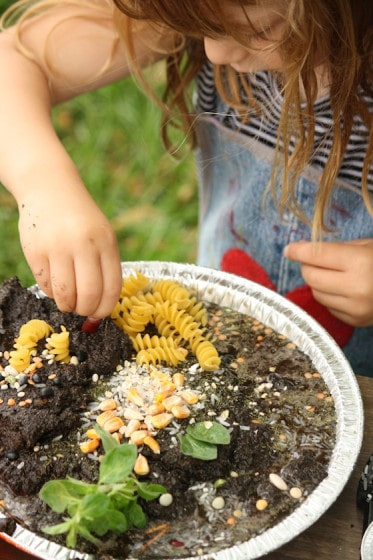 child decorating a mud pie with dried pasta and lentils