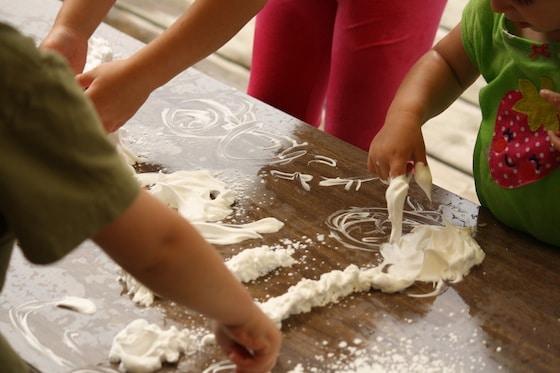 preschoolers exploring shaving cream on a table top