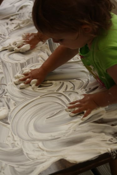 preschoolers swirling shaving cream on a table with their hands