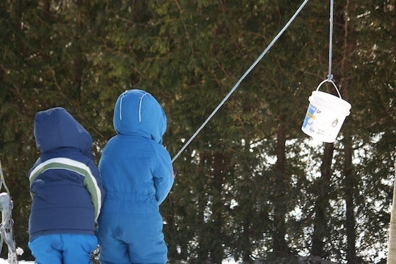 preschoolers in snow suits playing with bucket and rope contraption