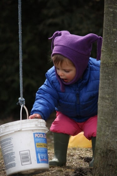 toddler investigating plastic bucket with top tied to handle