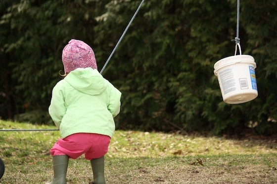 toddler hoisting a bucket with rope