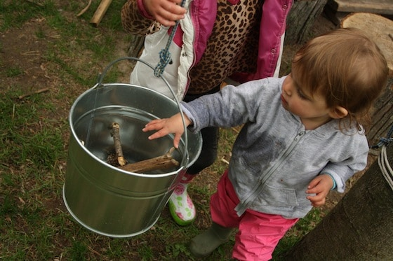 toddler loading up the bucket with sticks