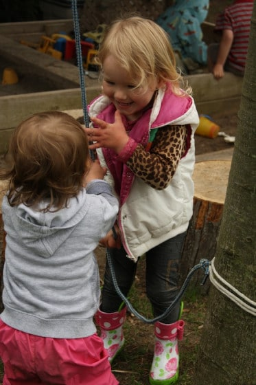 toddler and preschooler working together to lift the bucket