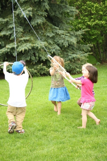 4 kids gathered around a hoola hoop and rope activity