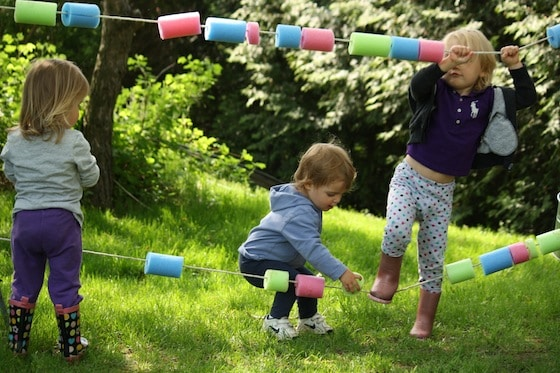 toddlers playing with giant abacus made from pool noodles and rope