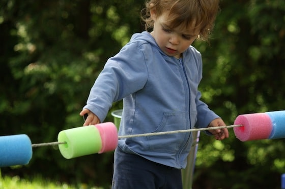 toddler playing with cut up pool noodles on rope