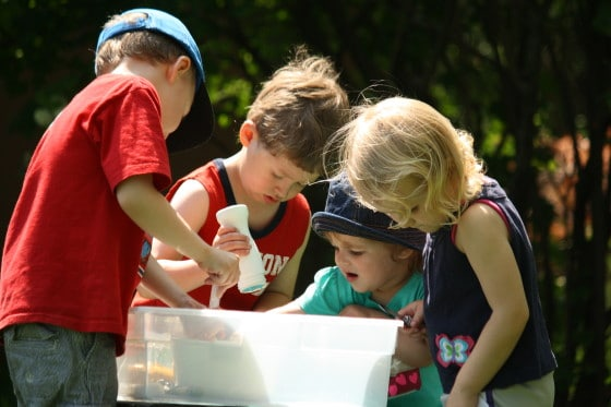 kids gathered around a sensory bin of ice and salt and water