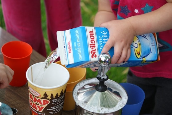 preschooler using cream carton filled with water for pretend play