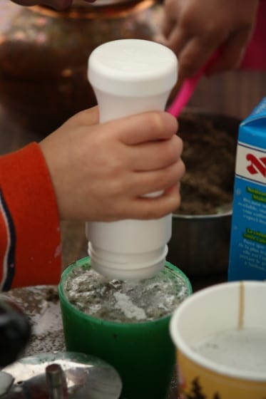 preschooler using shaker filled with sand